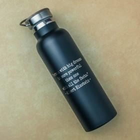 Detail textu vylaserovaného do černého povrchu nerezové láhve na pití.